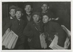 """A Lewis Hine photograph with the caption """"Group of newsboys starting out at Brooklyn Bridge early Sunday morning."""" The newsies got up every morning to pick up their bundle of newspapers. New York newspapers raised the price of these bundles during the Spanish-American War, when circulation increased. (Courtesy: boweryboyshistory.com)"""