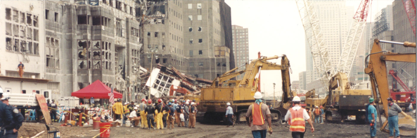 Workers, Fire Fighters, and Diggers Working and Broken Windows Visible in the Right Side