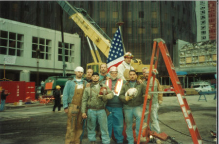 9 Unknown Workers Pose for a Photo With the Flag