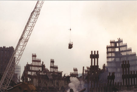 A Crane Lifting Men in a Box over Ground Zero and the Falling Exoskeleton