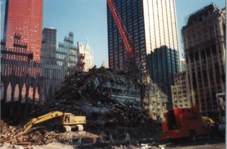 A Digger and Crane Working Through Debris infront of One Liberty Plaza, the Deutsche Bank Building, and 90 West St