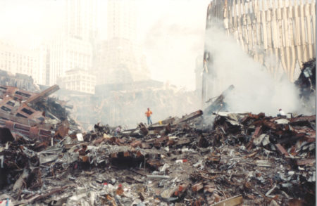 A Worker Standing on the Debris Surrounded by Smoke