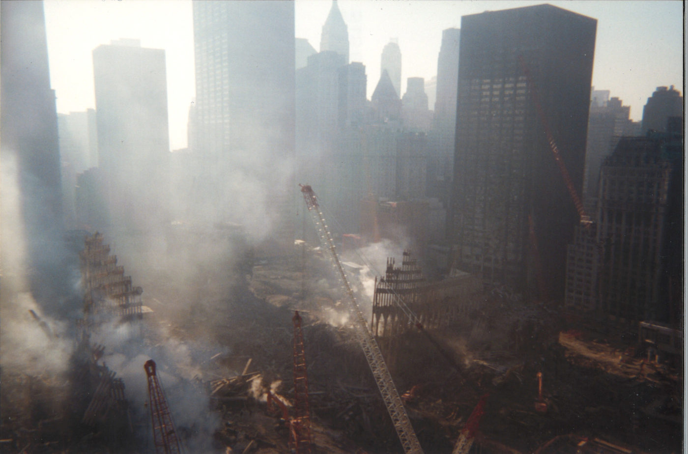 Aerial View of Exoskeleton of WTC 1 and 2 Surrounded by Smoke and Cranes