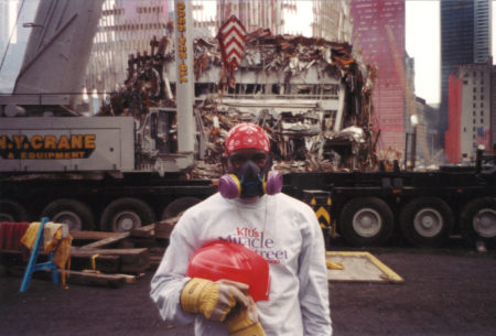 An Unknown Worker Wearing a Gas mask infront of the Crumbling WTC
