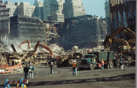 Clean up and Debris Removal at Ground Zero with Destroyed WTC5 in the Back