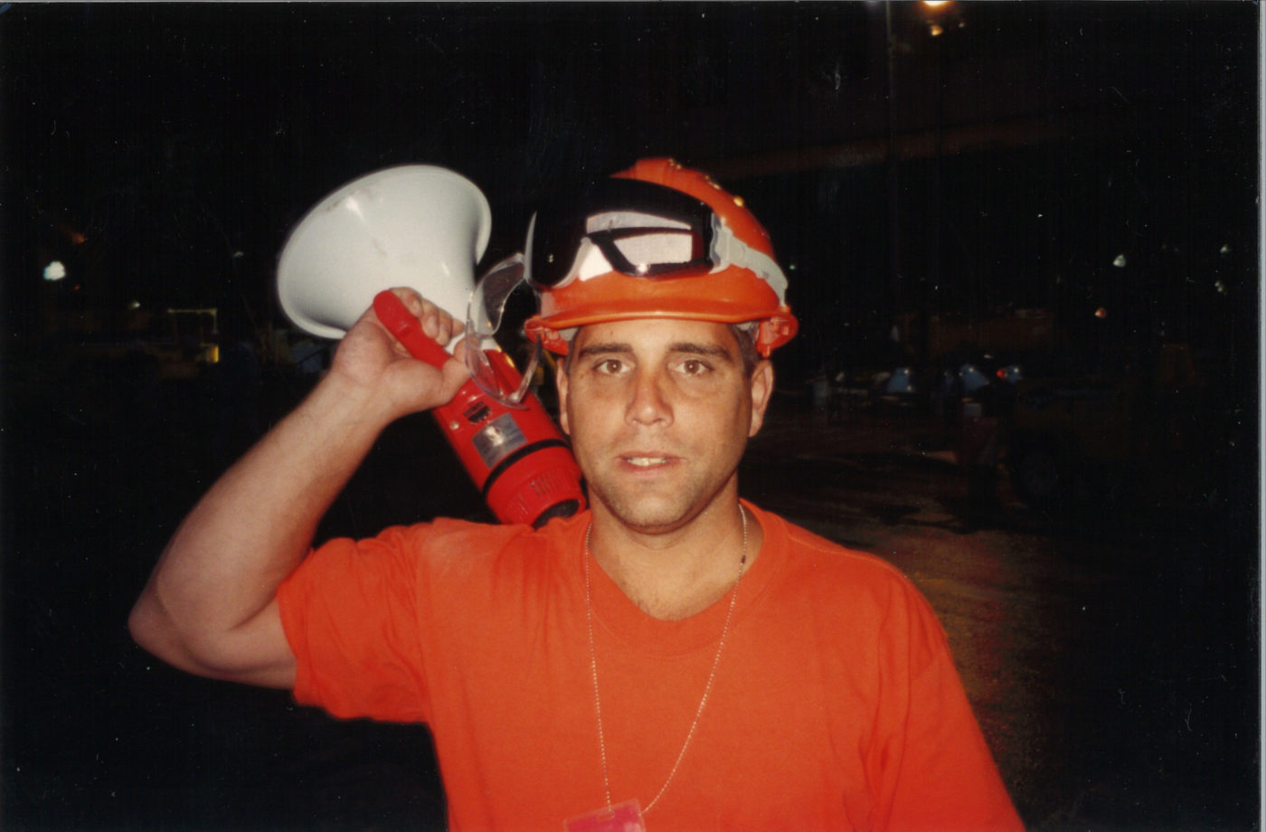 Closeup of an Unknown Worker With a Bullhorn at Night