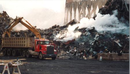 Crane Moving Debris into a Skip with Smoke Pouring Over Debris at Ground Zero