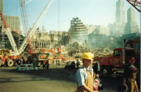 Cranes working at Ground Zero with Workers Walking in the Front