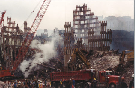 Diggers, Cranes, and Men working in Smoke with Falling Exoskeleton