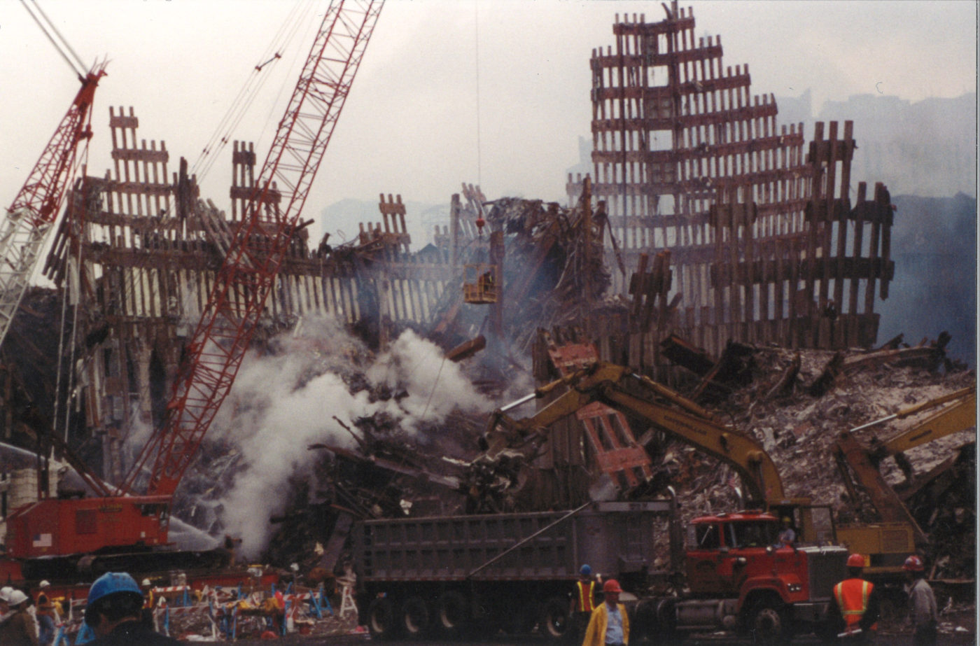 Diggers, cranes, dumptrucks, and men working in the still smoking rubble