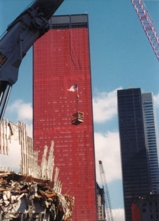 Falling Exoskeleton with a Crane Lifting a Box of Materials with an American Flag in the Back