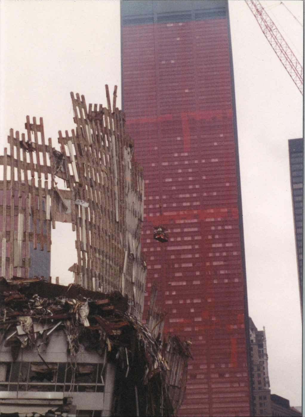 Falling Exoskeleton with workers in the a Crane Basket in front of Sheathed One Liberty Plaza