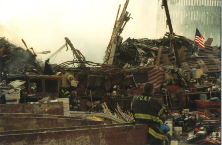 Fire Fighter Standing near Debris and Heavy Machinery