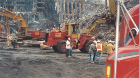 Ground Level Shot of Workers Surrounded by Wrok Trucks at Ground Zero