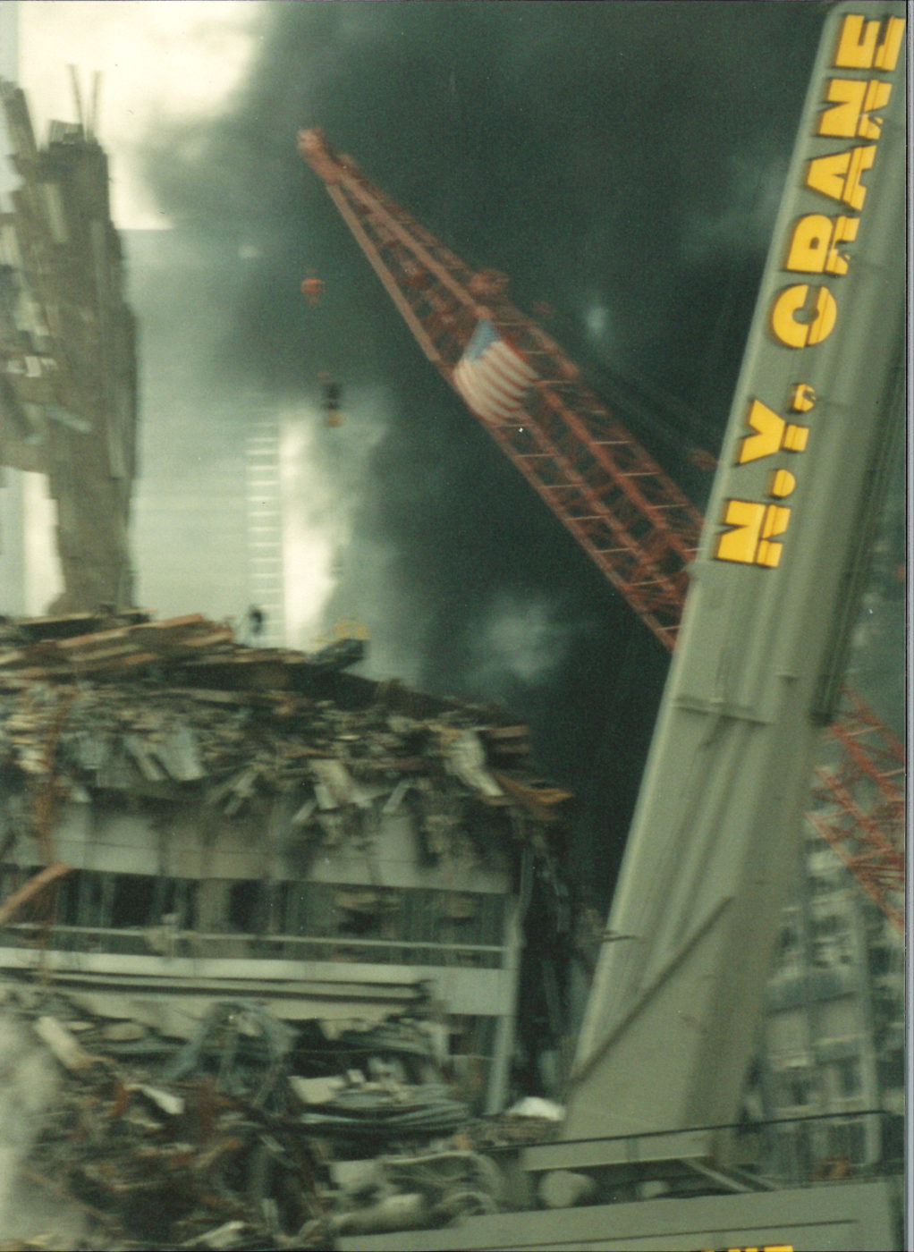 New york Crane with collapsed building and thick black smoke behind
