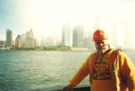 Photo of unknown worker from the water with the Battery and smoke-filled downtown skyline behind.