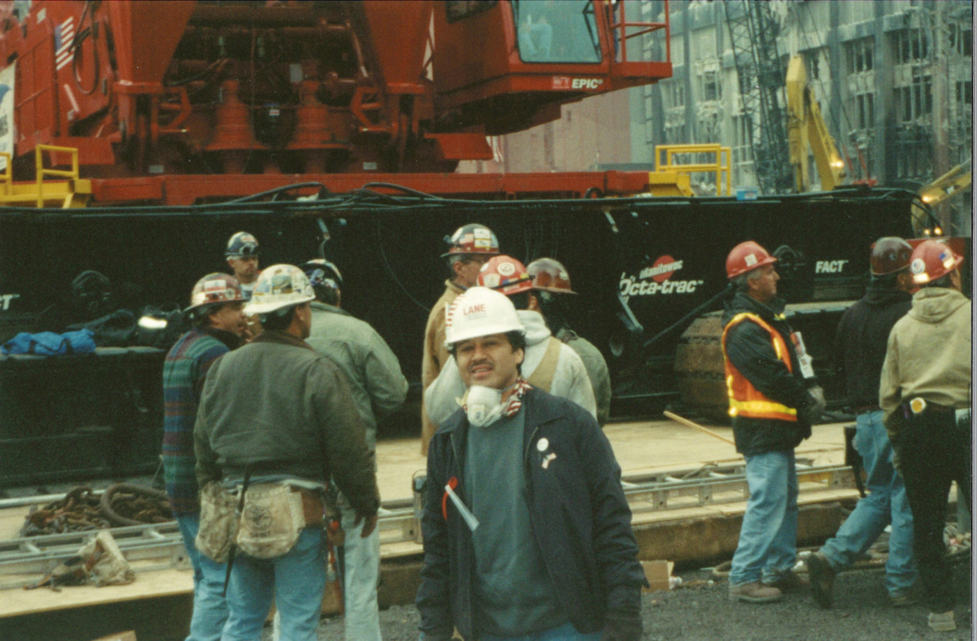 Photo of Workers Standing Together infront of a Crane on a Cold Day at Ground Zero