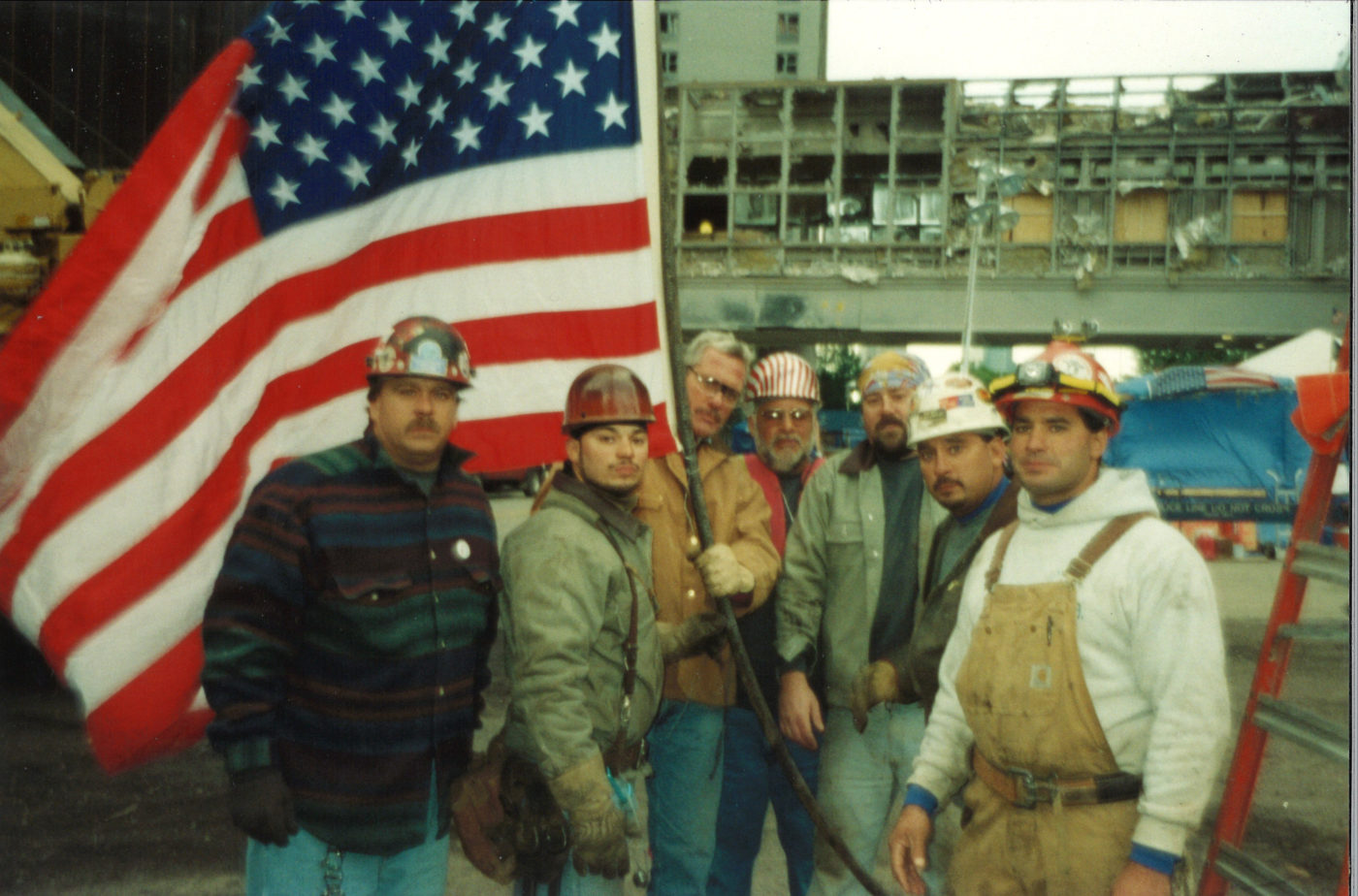 Seven Unknown Workers Take a Photo with the Flag