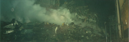 Smoke Pouring Over Rubble with Barely Visible Workers at Night