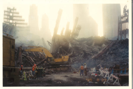 Smoky image of workers at Ground Zero with skeletal remains of WTC