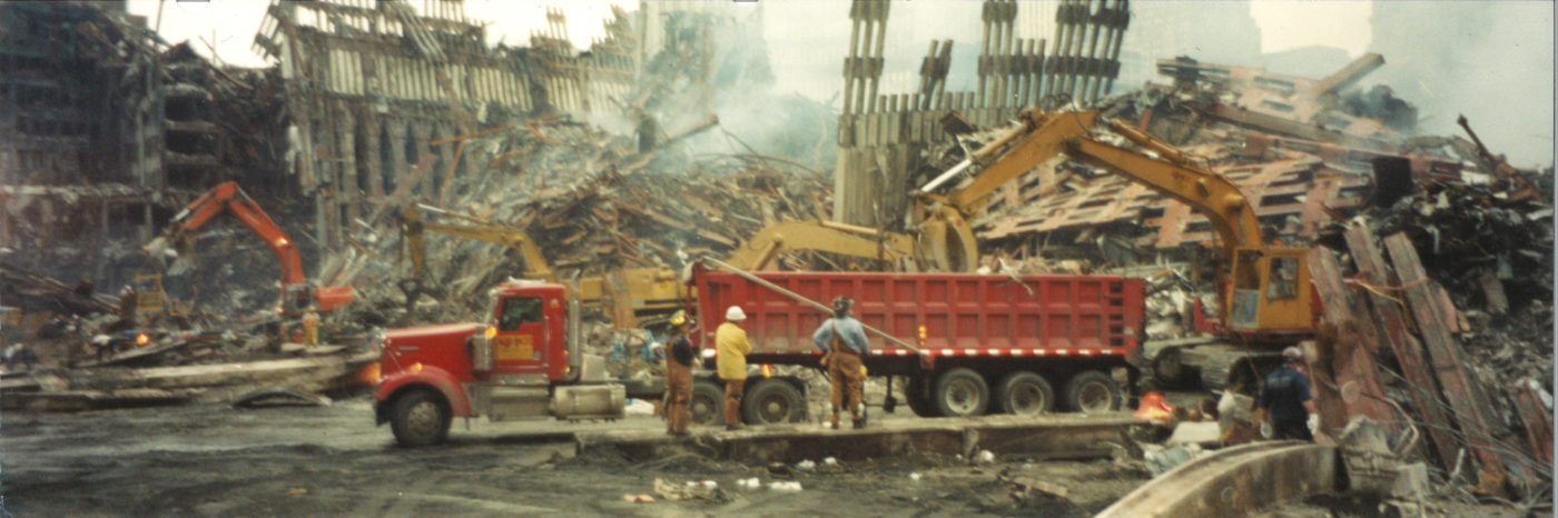 Three Workers Watching Debris Being Lifted into the back of a Skip