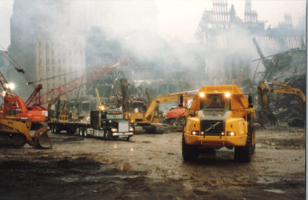 Trucks on West Street in front of the remains of Tower 1 and WTC 6