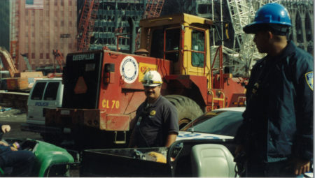 Two Unknown Workers Standing Amongst Heavy Machinery at Ground Zero