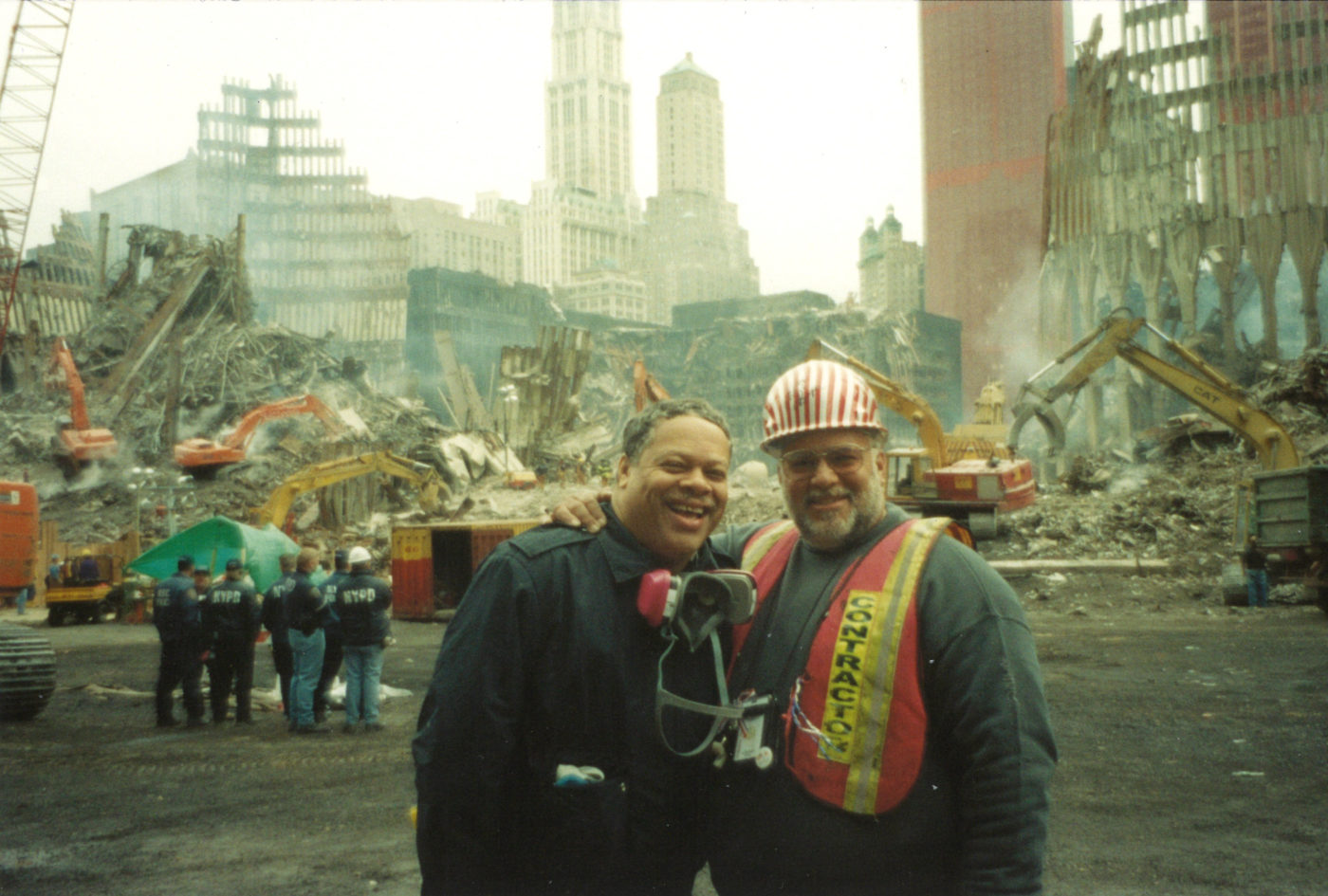 Two Unknown Workers Take a Photo with Work in the Backgroudn and a Group of NYPD Officers Standing in the Back