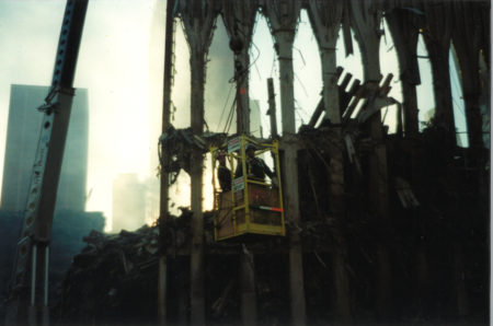 Two Workers in a Crane Box Beside the Falling Exoskeleton of the WTC