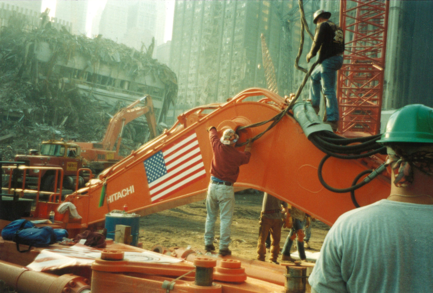 Two Workers Repairing a Digger Arm at Ground Zero