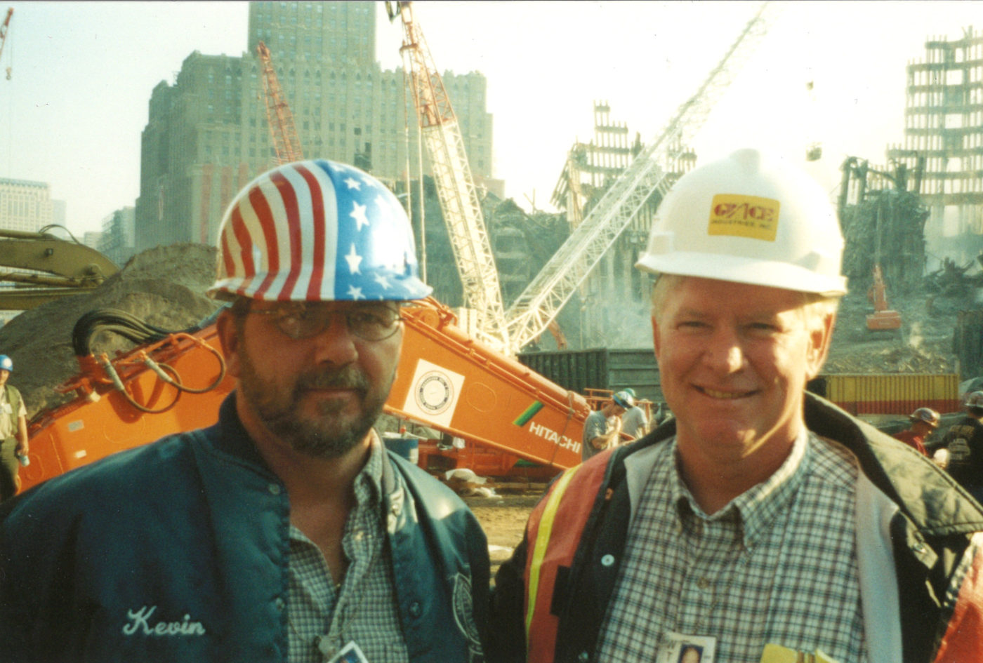 Two Workers Take Photo at Ground Zero, One is Wearing an American Flag Hat