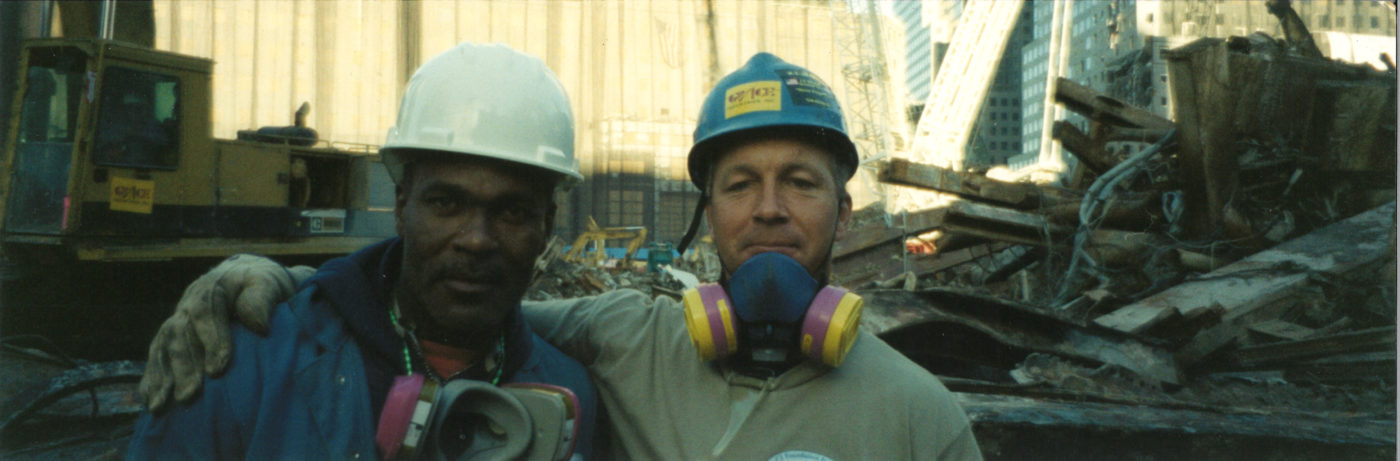 Two Workers with Gas Mask Embrace and Take a Photo at Ground Zero
