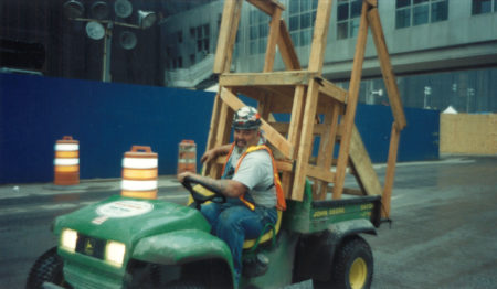 Unknown Worker Driving a Wooden Stair on the Back of a Cart Through Ground Zero