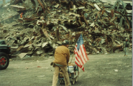 Unknown Worker Moving Materials with an American Flag On the Cart
