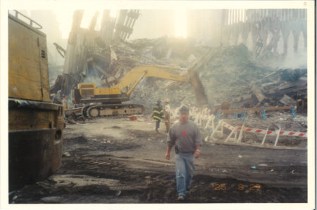 Unknown Worker Walking in Ground Zero, with Two Fire Fighters Standing on Debris in the Back