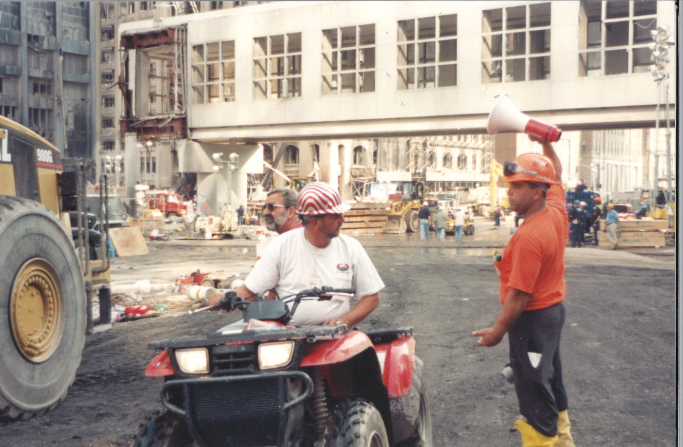 Unknown Workers Looking at Each other as one uses a Bullhorn at Ground Zero