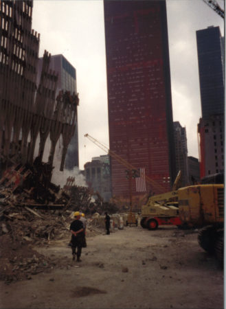 Work at Ground Zero in front of falling exoskeleton and a sheathed One Liberty Plaza