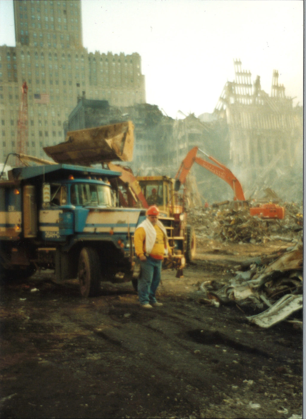 Worker Standing infront of a Truck and Digger at Ground Zero with 140 West St in the Back