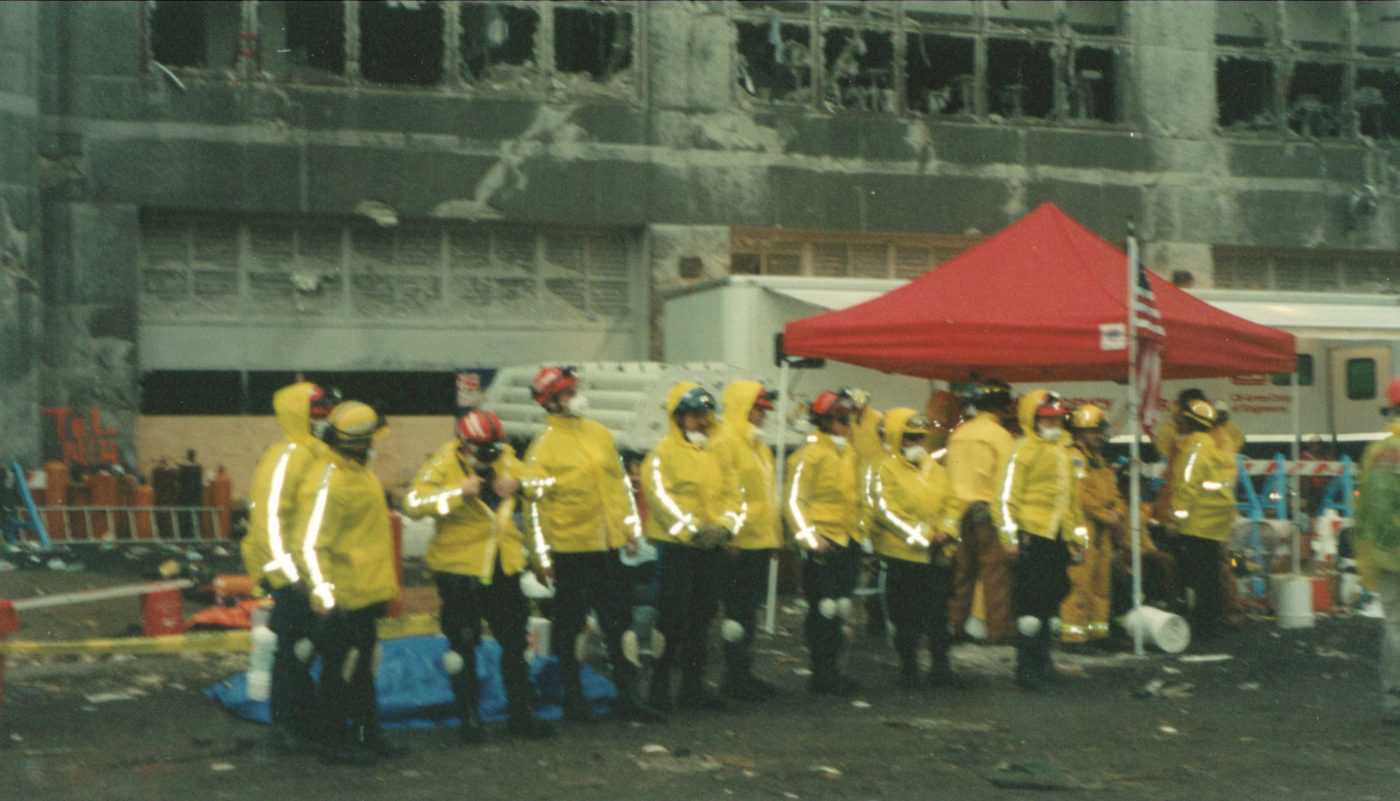 Workers Stand in HighVis Jackets near Tent