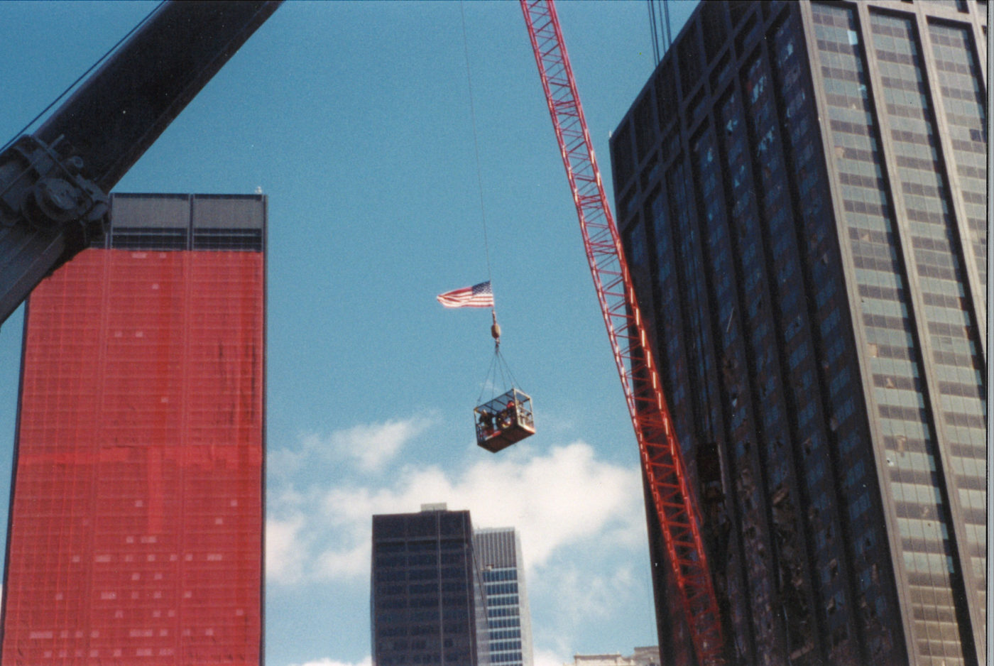 Workers Suspended in a Crane Basket with One Liberty Plaza and the Deutsche Bank Building in the Back