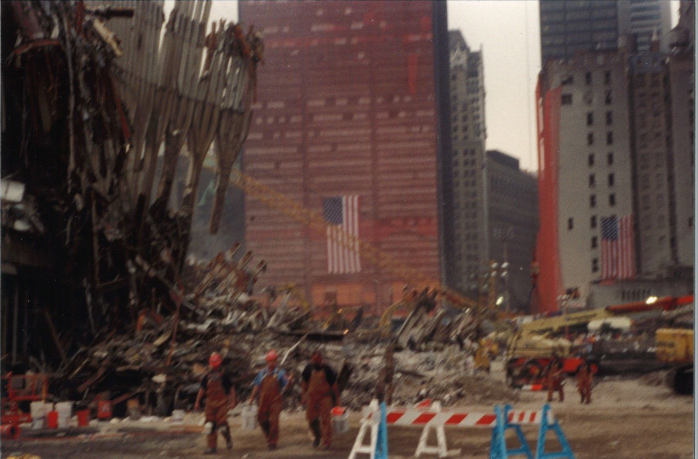 Workers Walking Near Falling Exoskeleton with Sheathed One Liberty Plaza in the Back