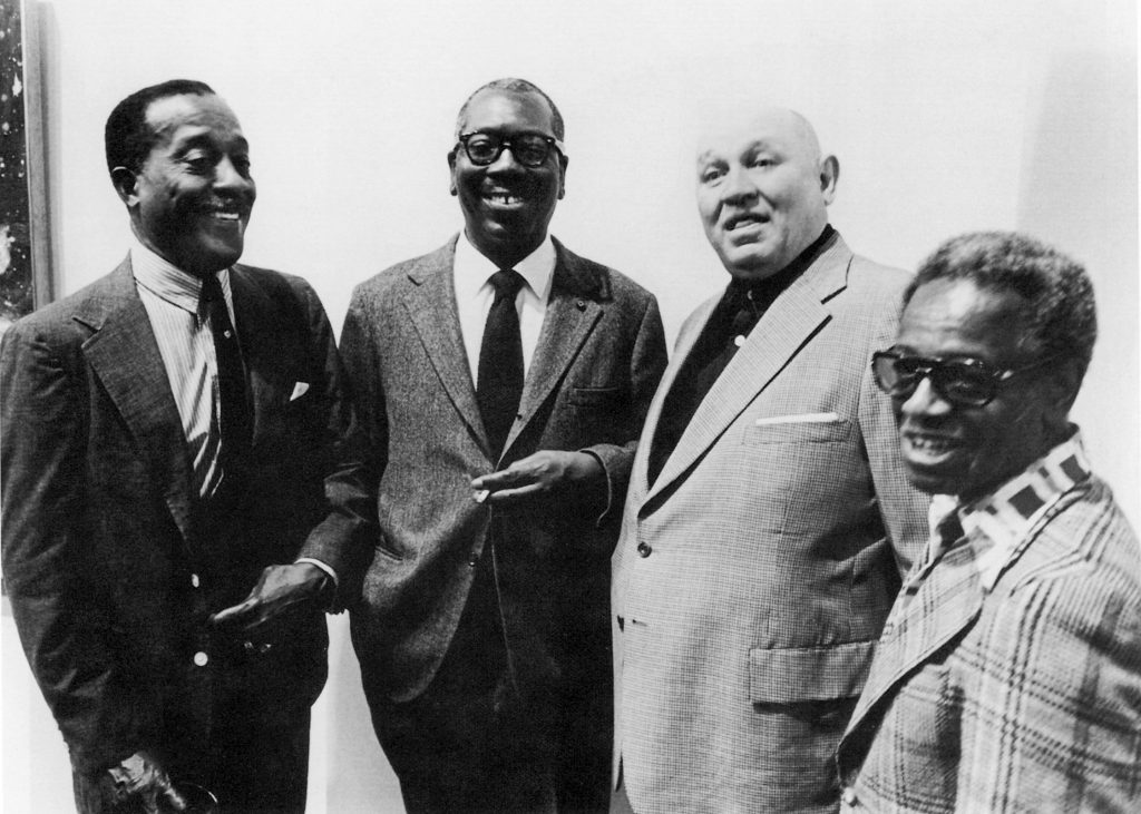 """Norman Lewis, Jacob Lawrence, Romare Bearden, and Ernest Crichlow (ca. 1970). Photo courtesy of """"Charles Alston and the '306' Legacy"""" Cinque Gallery exhibition catalog (2000) via Artnet."""