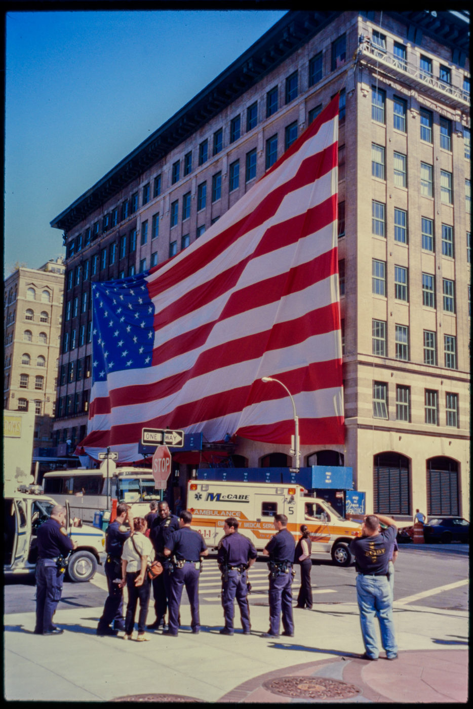 Ambulance Passes as Police and Passerby Stand Near American Flag at Hubert and Greenwich Streets.jpg