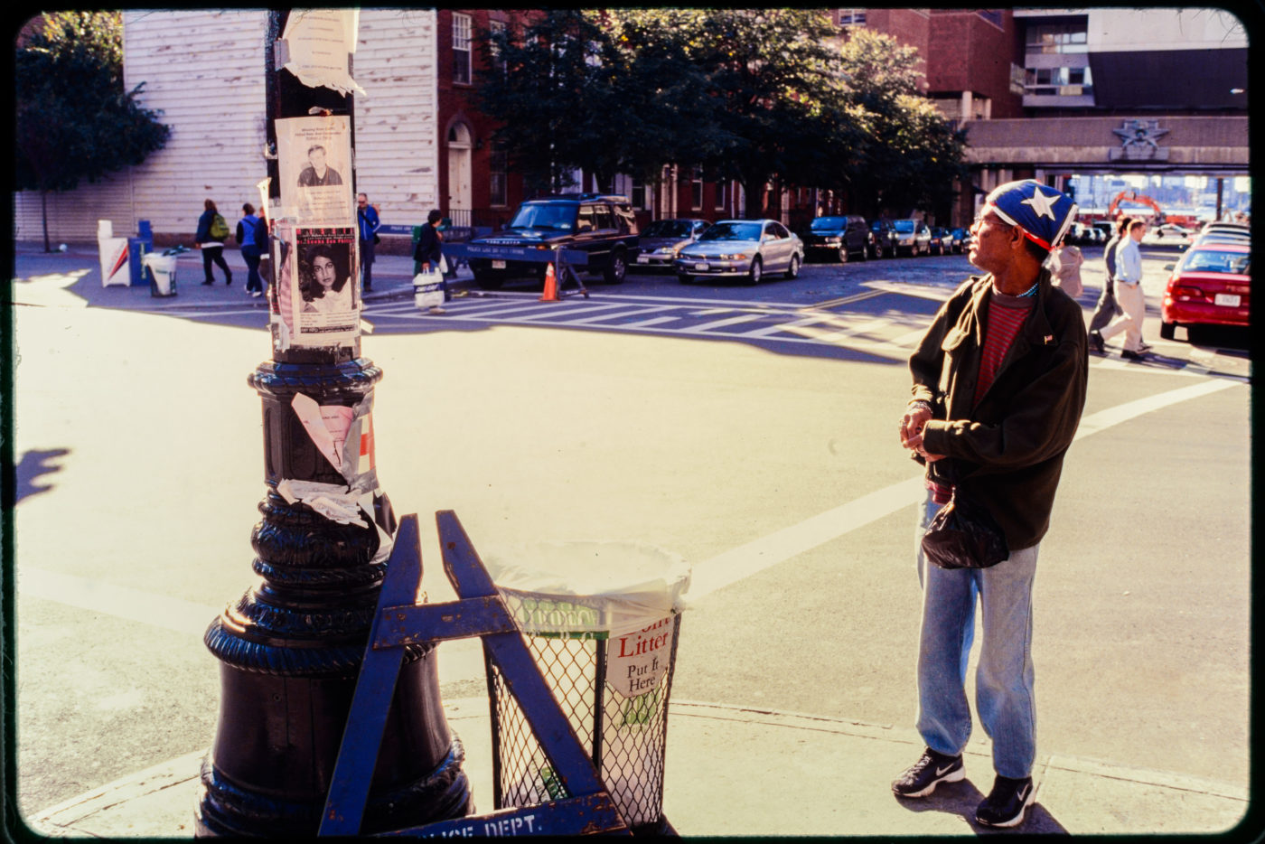 An Individual Pauses by Memorial and Missing Persons Lightpost at the Corner of Harrison and Greenwich Streets.jpg