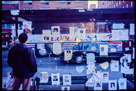 An Unknown Pedestrian Looks Through Flyers for Missing Loved Ones Attached to a Bus Station as a Coach USA Bus Passes By.jpg