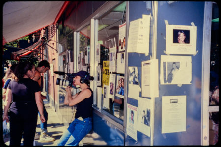 Flyers of Missing Loved Ones Cover Italian Ice Shop Window, New Yorkers Stand Outside and Pass By as an Individual Captures Them on A Camera.jpg