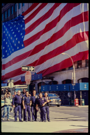 Group of Police Officers Pose in Front of Enormous American Flag at Hubert and Greenwich Streets, Individual with a Video Camera Stands Behind Them.jpg