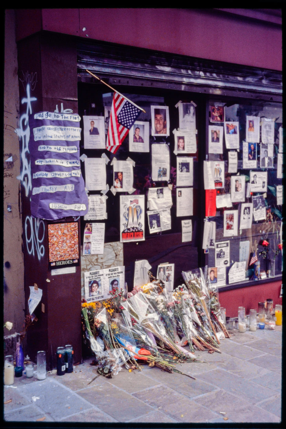 Memorial and Missing Persons Wall on the Side of Building, Flowers and Prayer Candles Left Along Border.jpg