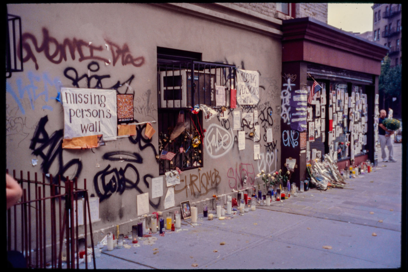 Missing Persons Wall on the Side of a Building, Flowers and Candles Left.jpg