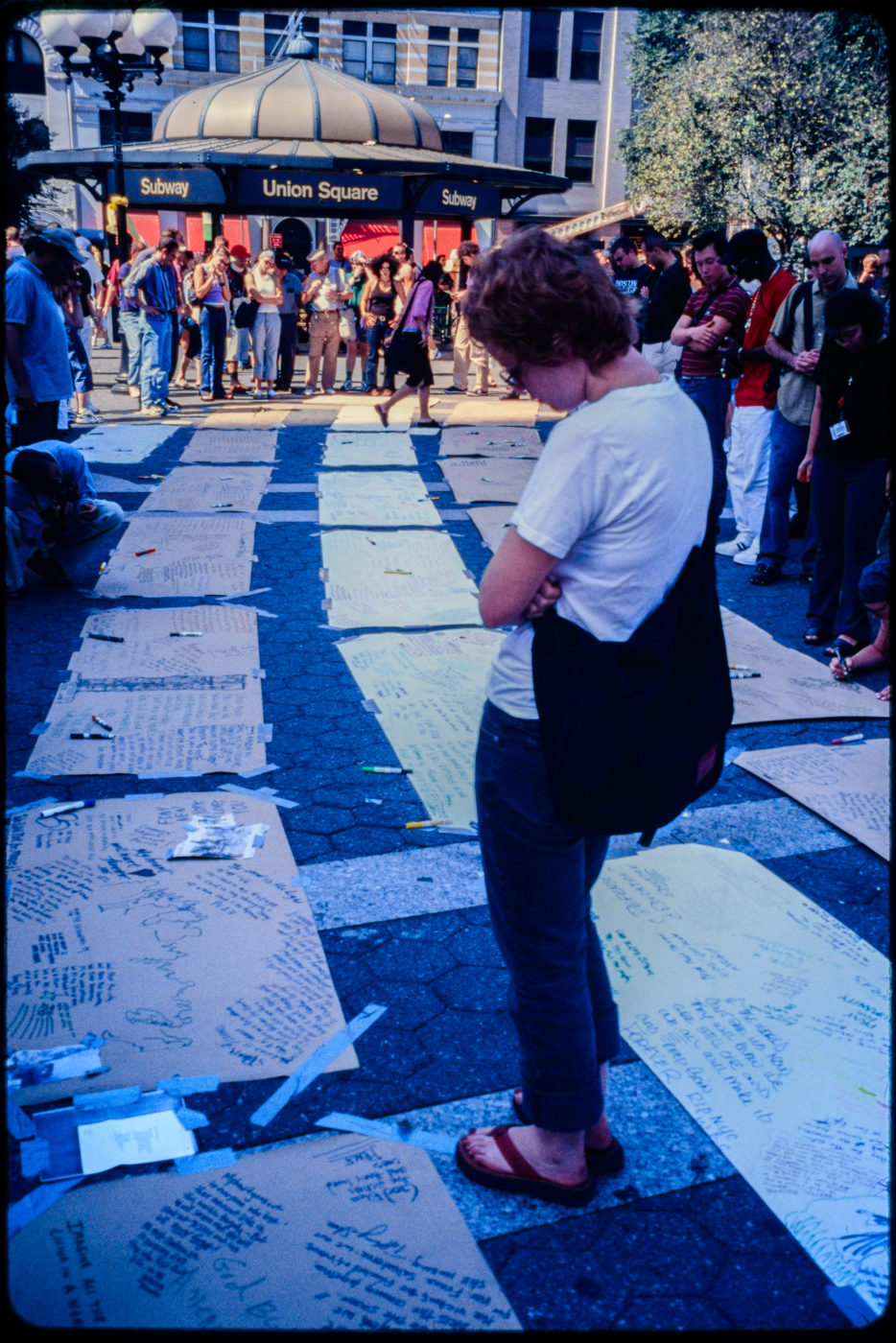 One Individual Stands Reading Messages Left at Union Square Park Memorial Between Rows of Cardboard, Other New Yorkers Gather Nearby.jpg